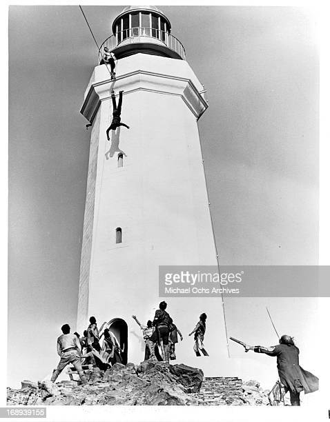 Kirk Douglas dangles from a lighthouse in a scene from the film 'The Light At The Edge Of The World' 1971