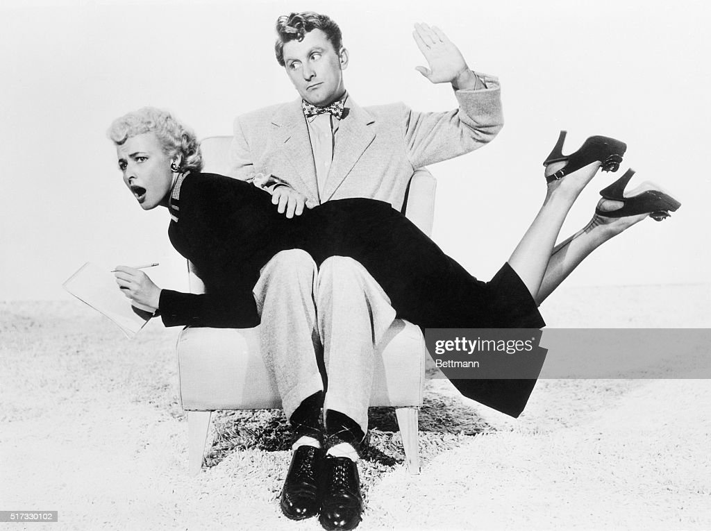 Kirk Douglas with Laraine Day over His Knee : News Photo