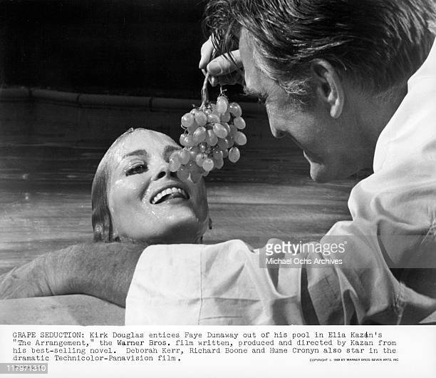 Kirk Douglas holding a bunch of grapes towards Faye Dunaway in a scene from the film 'The Arrangement' 1969