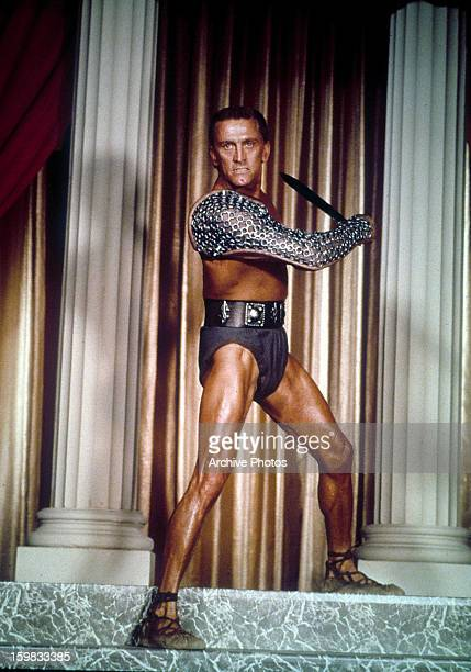 Kirk Douglas the slave Spartacus standing in between columns holding a sword in a scene from the film 'Spartacus' 1960