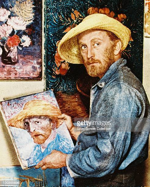 Kirk Douglas US actor with a beard and straw hat posing in front of a selfportrait in a publicity still issued for the film Lust for Life' 1956 The...