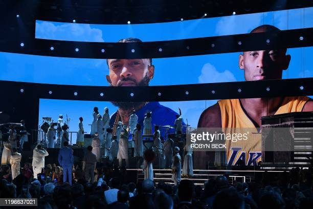 Kirk Franklin John Legend and Dj Khaled perform onstage while Nipsey Hussel and Kobe Bryant images appear on screen during the 62nd Annual Grammy...