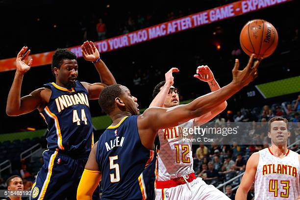 Kirk Hinrich of the Atlanta Hawks loses the ball as he drives against Solomon Hill and Lavoy Allen of the Indiana Pacers at Philips Arena on March 13...