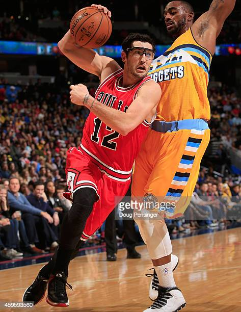 Kirk Hinrich of the Chicago Bulls controls the ball against Darrell Arthur of the Denver Nuggets at Pepsi Center on November 25 2014 in Denver...