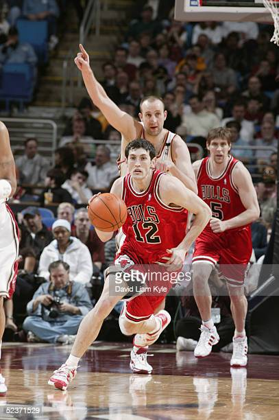 Kirk Hinrich of the Chicago Bulls drives around Zydrunas Ilgauskas of the Cleveland Cavaliers during the game at Gund Arena on February 23, 2005 in...