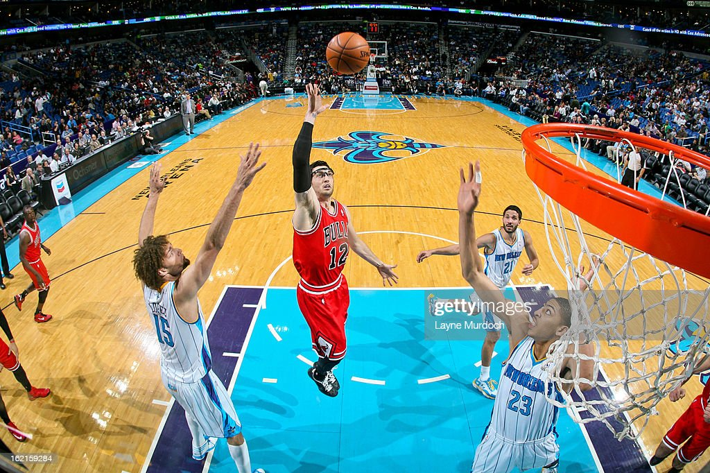 Kirk Hinrich #12 of the Chicago Bulls shoots in the lane against Robin Lopez #15 and Anthony Davis #23 of the New Orleans Hornets on February 19, 2013 at the New Orleans Arena in New Orleans, Louisiana.