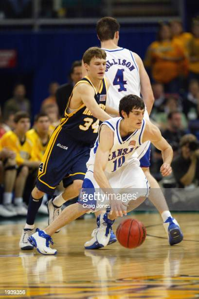 Kirk Hinrich of the University of Kansas Jayhawks drives past Travis Diener of Marquette University Golden Eagles during the semifinal round of the...