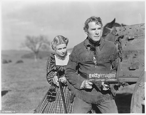 Kirk Jordan and Ivy Preston stand alongside a wagon brandishing guns in a scene from the 1938 western The Texans