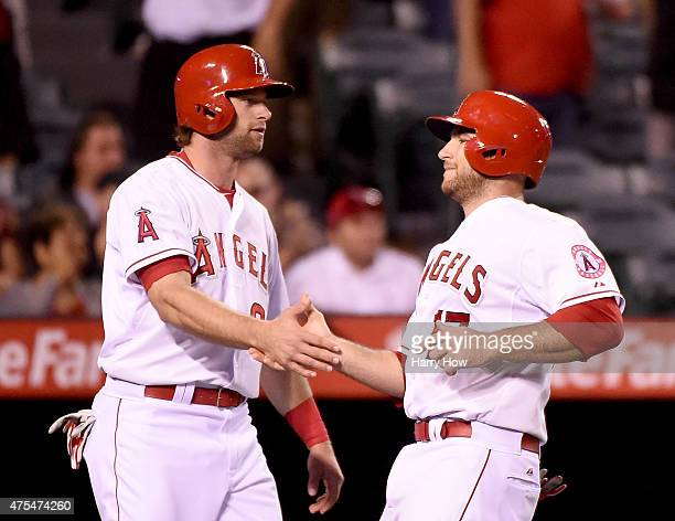 Kirk Nieuwenhuis and Chris Iannetta of the Los Angeles Angels celebrate their runs from a Johnny Giavotella hit to take a 42 lead during the ninth...