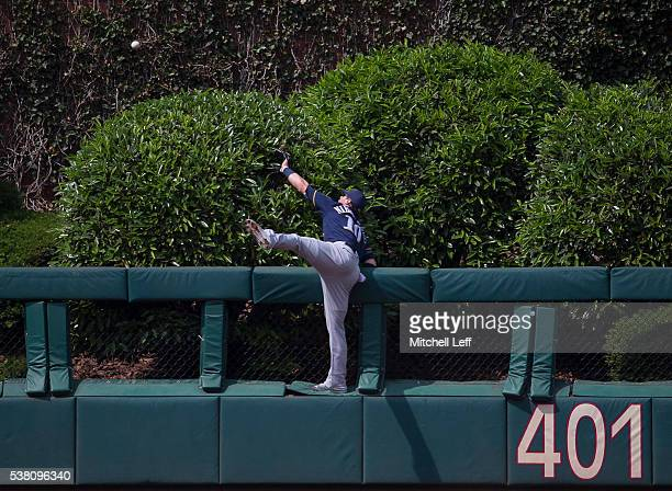 Kirk Nieuwenhuis of the Milwaukee Brewers climbs the wall and watches as the ball hit by Tommy Joseph of the Philadelphia Phillies goes over the...