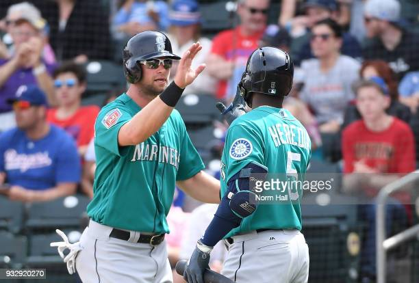Kirk Nieuwenhuis of the Seattle Mariners is congratulated by teammate Guillermo Heredia after scoring on a hit by Jean Segura against the Texas...