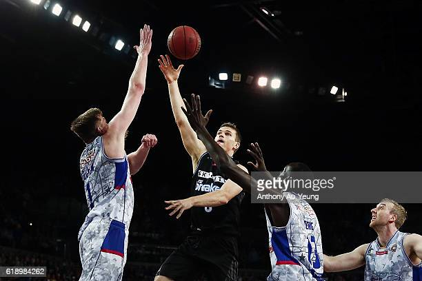 Kirk Penney of New Zealand shoots against Matt Hodgson and Majok Deng of Adelaide during the round four NBL match between the New Zealand Breakers...