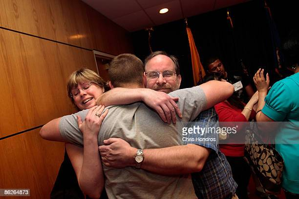 Kirk Petersen hugs his son Harry Petersen along with his stepmother Nina Nicholson after he took the Oath of Enlistment to join the US Navy April 28...