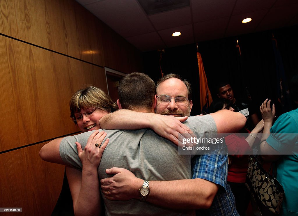 Kirk Petersen (R), of Maplewood, New Jersey, hugs his son Harry Petersen, 21, along with Harry's stepmother Nina Nicholson (L), after he took the Oath of Enlistment to join the US Navy April 28, 2009 at Fort Hamilton in the Brooklyn borough of New York City. Nearly 8000 local recruits for the military's five service branches are processed through Ft. Hamilton's Military Entrance Processing Station every year, getting medical tests, background checks and taking an oath of allegiance before being sent off to camp for basic training.