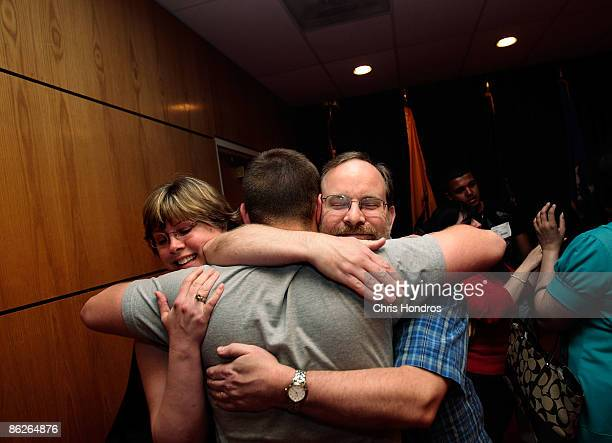 Kirk Petersen of Maplewood New Jersey hugs his son Harry Petersen along with Harry's stepmother Nina Nicholson after he took the Oath of Enlistment...