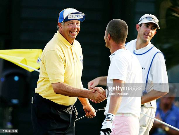 Kirk Triplett shakes hands with Jesper Parnevik of Sweden shakes on the 18th green on the Copperhead Course at the Innisbrook Resort during the final...