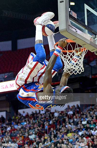 Kirk 'Zeus' Stewart of the Harlem Globetrotters dunks using his feet during a trick shot challenge against the World AllStars during an exhibition...
