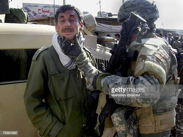 A US soldier inspects a wounded man at the site where two car bombs exploded in quick succession at a garage in the oil rich city of Kirkuk north of...