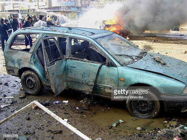 An Iraqi firefighter douses fire which swept over a vehicle at the site where two car bombs exploded in quick succession at a garage in the oil rich...