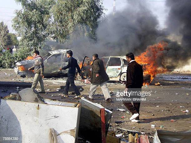 Iraqis rush to the site where two car bombs exploded in quick succession at a garage in the oil rich city of Kirkuk north of Baghdad 17 February 2007...