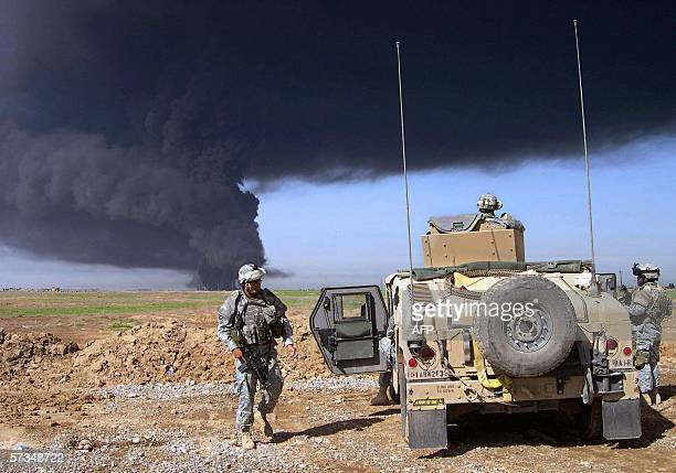 TO GO WITH A STORY BY PAUL SCHEMM US soldiers from the 1st Brigade of the 101st Airborne division watch as smoke from an oil fire covers the sky...
