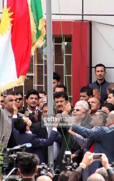Kirkuk provincial Governor Najim alDin Karim raises the Kurdish flag to fly next to an Iraqi flag over a government building in the northern Iraqi...