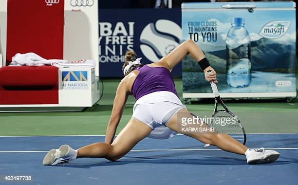 Kirsten Flipkens of Belgium falls as she plays a shot against Alize Cornet of France during the 1st Round of the WTA Dubai Duty Free Tennis...