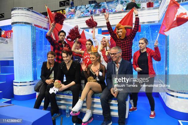 KirstenMooreTowers and MichaelMarinaro of Canada wait for their score at the kiss and cry with their team mates after competing in the Pair Free...
