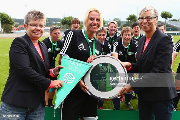 Kirstin Petry of SG Dirmingen receives the trophy from Kathrin Nicklas and Sabine Mammitzsch afterher team won the DFB Women's Over35 Cup on...