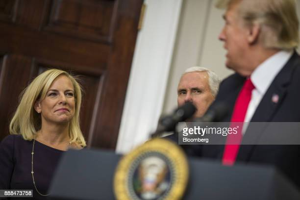 Kirstjen Nielsen secretary of Homeland Security left and US Vice President Mike Pence center listen as US President Donald Trump speaks during a...