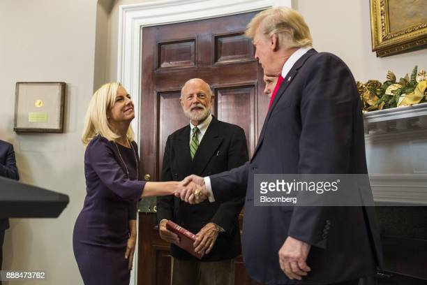 Kirstjen Nielsen secretary of Homeland Security left shakes hands with US President Donald Trump after being sworn in during a ceremony in the...