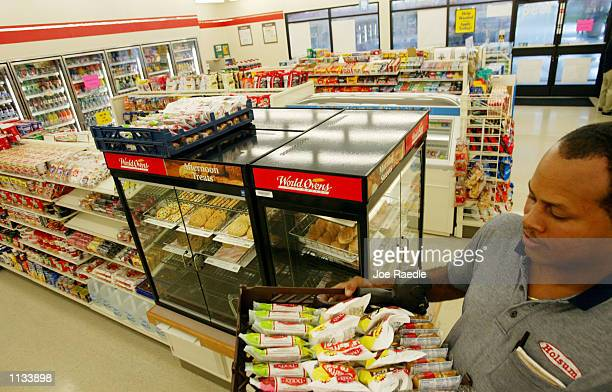Kirt Smith delivers a tray of pies and other sweets from Holsum foods to the 7Eleven store on July 18 2002 in Pembroke Pines Florida 7Eleven Inc the...