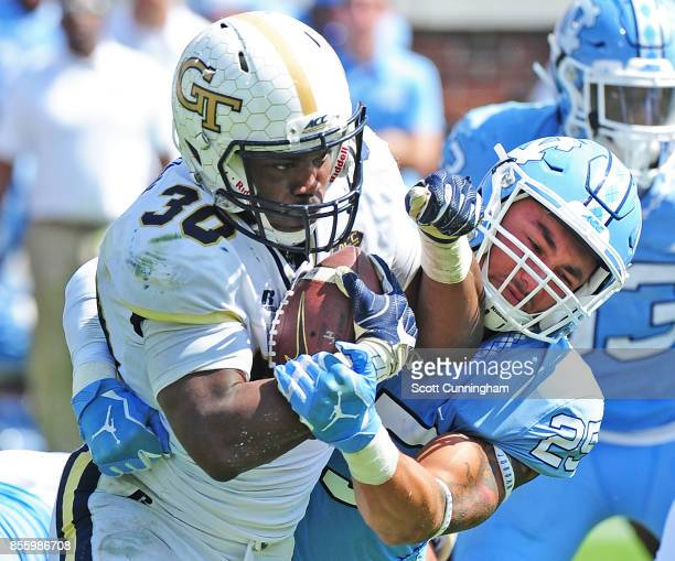KirVonte Benson of the Georgia Tech Yellow Jackets fights for yardage against Ayden Bonilla of the North Carolina Tar Heels on September 30 2017 in...