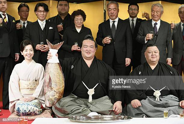 Kisenosato flanked by his stablemaster Tagonoura and the stablemaster's wife lifts a sea bream a fish eaten during celebrations in Japan after...