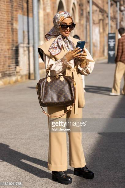 Kishama Meridian wears a Zara jacket and pant with Louis Vuitton boots and bag and a vintage scarf at Afterpay Australian Fashion Week 2021 on June...