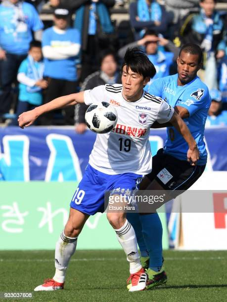 Kisho Yano of Albirex Niigata and Calvin Jong A Pin of Yokohama FC compete for the ball during the JLeague J2 match between Yokohama FC and Albirex...