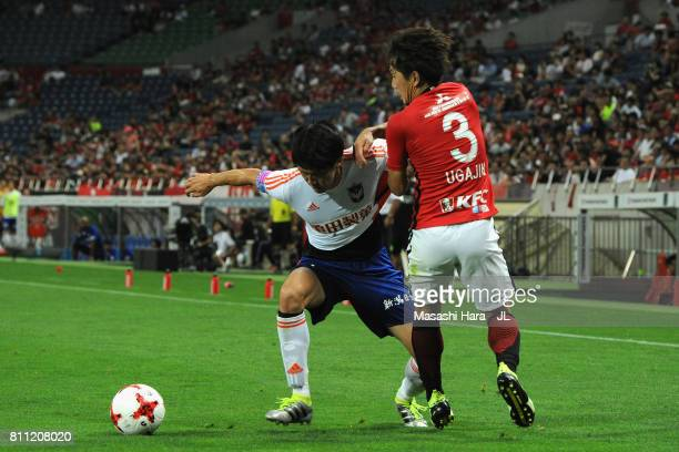 Kisho Yano of Albirex Niigata and Tomoya Ugajin of Urawa Red Diamonds compete for the ball during the JLeague J1 match between Urawa Red Diamonds and...