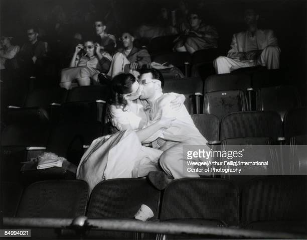 a woman and man kissing while wearing 3D glasses in a movie theatre New York ca1943 Photo by Weegee/International Center of Photography/Getty Images