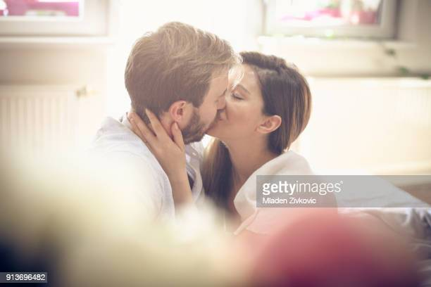 kiss in bed. - good morning kiss images stock photos and pictures