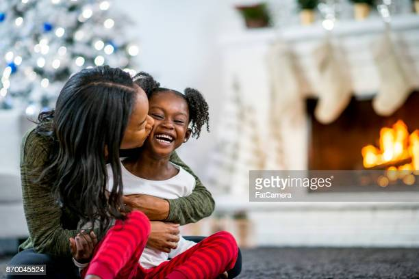 kiss on the cheek - winter family stock photos and pictures