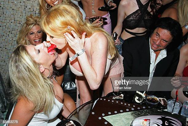 Kiss singer/bassist Gene Simmons watches as adult film actresses Sara Jay and Taylor Wane play with the tongue from his birthday cake during his...