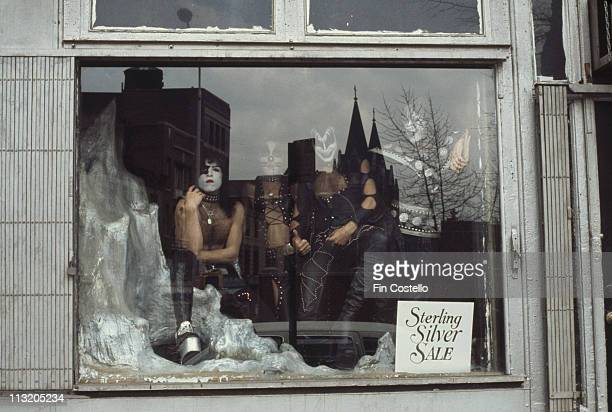 Kiss US rock band pose for a group portrait in a shop window with a sign reading 'Sterling silver sale' circa 1975
