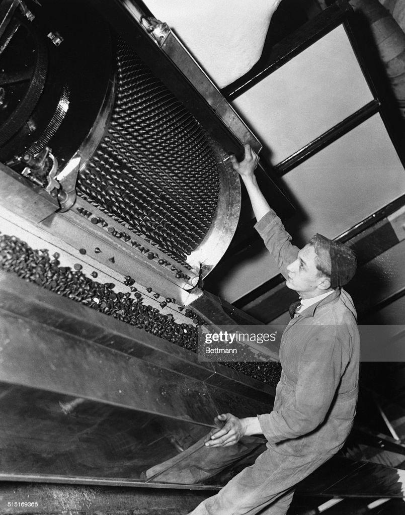 Man Watches Machine Making Hershey's Kisses in Factory : News Photo