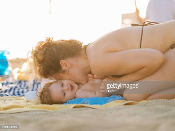 Kissing and hugging cute baby on the beach