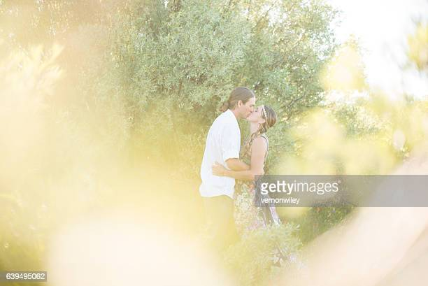Kissing behind leafy trees