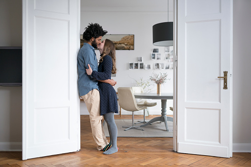 Kissing couple at home standing in door frame in living room - gettyimageskorea