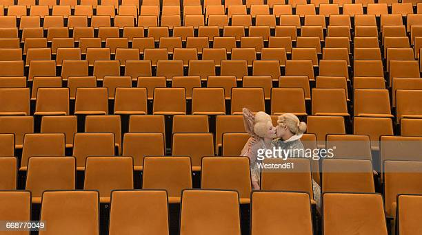 Kissing couple dressed in Baroque costumes sitting in an empty auditorium of a theatre