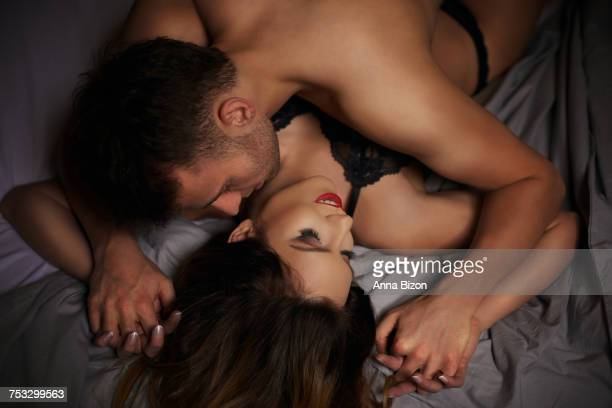 Kissing couple holding hands in bed. Debica, Poland