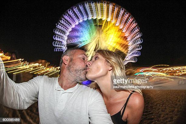 Kissing couple in front of rainbow big wheel