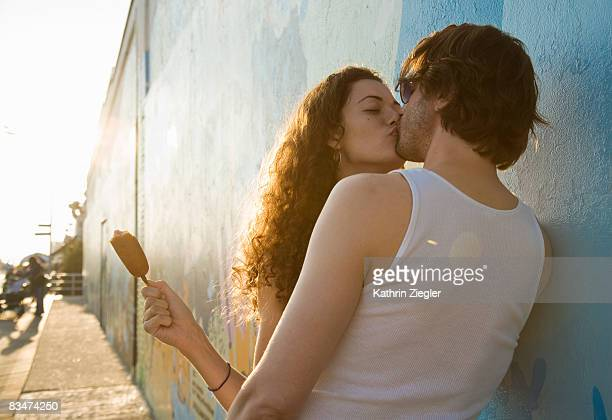kissing couple leaning against wall - besar fotografías e imágenes de stock